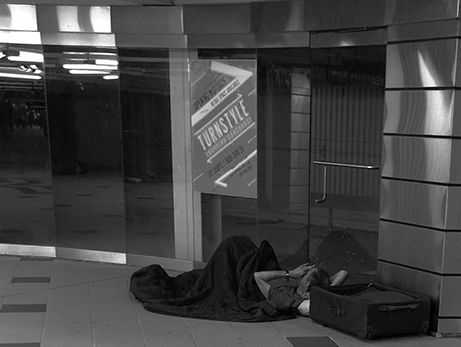 Homeless Individual Sleeping In Front of a Turnstyle Storefront
